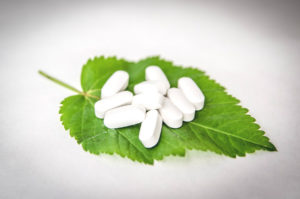 "supplement pills on a leaf surrounding the question ""how many supplements can someone take?"""