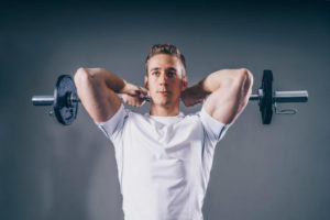 muscular and strong man lifting weights