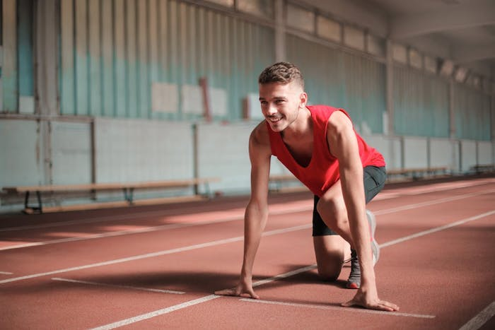 man looking energised on a sprinting track read to set off